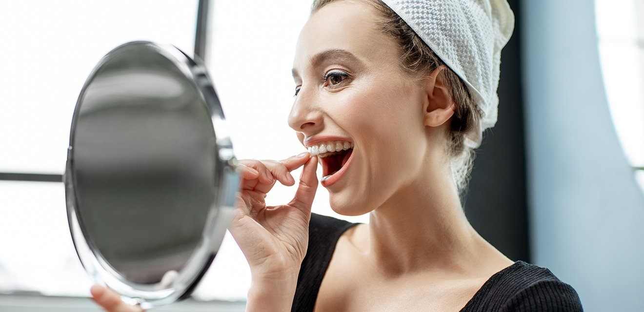 woman looking at herself putting in invisalign