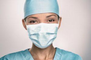 smiling dental team member in PPE to prevent COVID-19